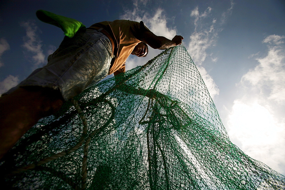 A fisherman straightens nets on the docks of Joshua's Marina in Buras, Louisiana.