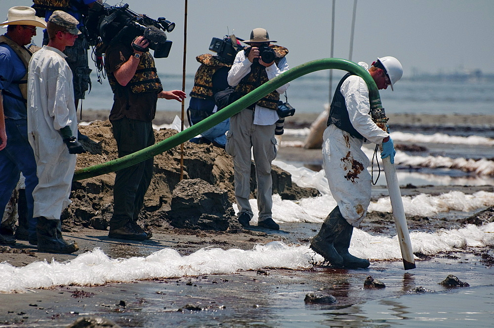 Clean-up crews sucking oil with vacuum tubes and placing absorbent pompom booms.   East Grand Terre was involved in a Barrier Island restoration project before the oil spill.