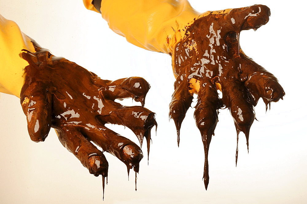 The site of the BP Deepwater Horizon oil drilling catastrophe: Gloved hands with thick, dripping oil