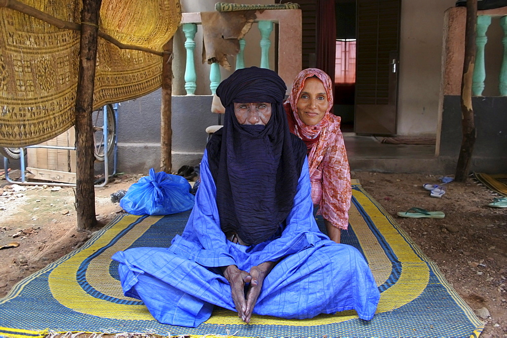A Muslim Toureg husband and wife sitting on a mat wearing turban and shawl, Mali, West Africa