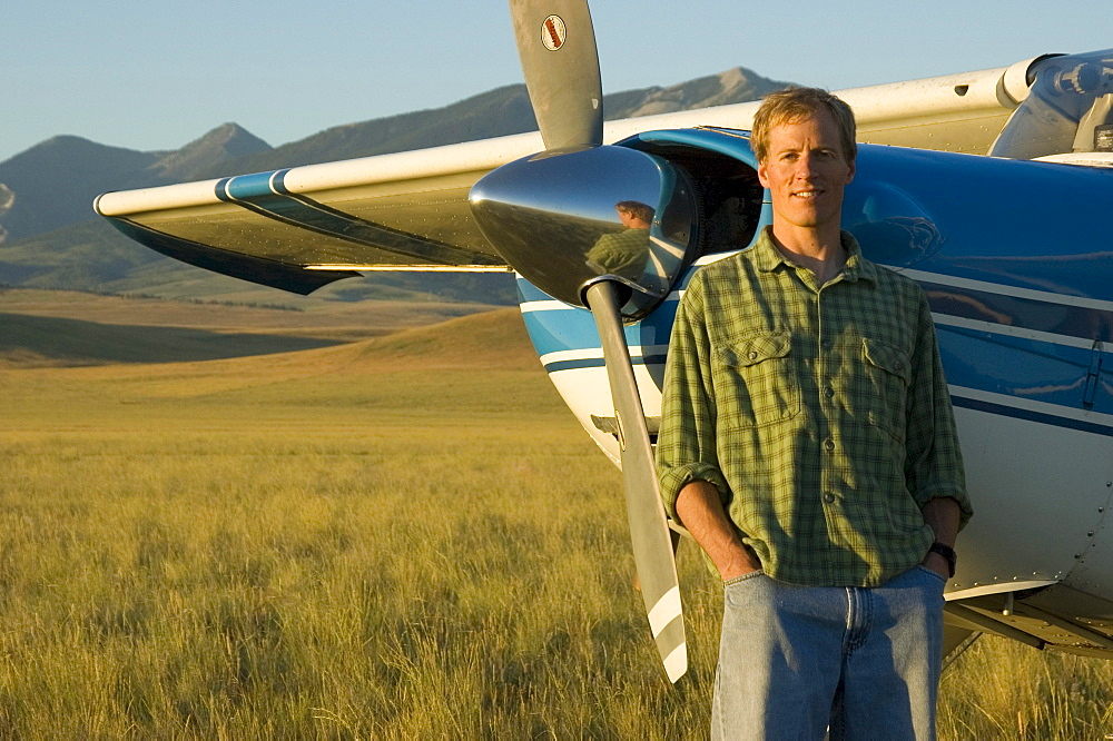 A man stands in a field next to his Cessna airplane with mountains in the background near Bozeman, Montana.
