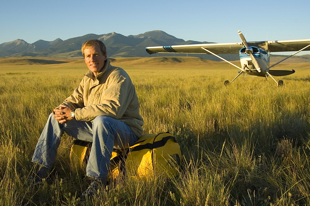 A man sits in a field next to his airplane with mountains in the background near Bozeman, Montana.