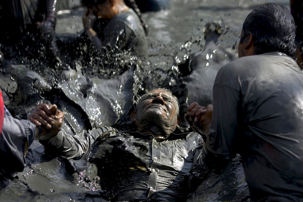 An old man is healed in the mud baths of Espinoza, Mexico.Twice a year the faithful visit Espinazo, a small dusty village and birthplace of El Nino Fidencio, one of the most revered healers in North East Mexico.  Although he died in the 1940s people believe certain priests known as Materias can channel his healing gifts and cure people.  During the anniversary of his birth and death over 100,000 people take part in the celebration by giving thanks at his gravesite or bathing and getting healed in mud baths.