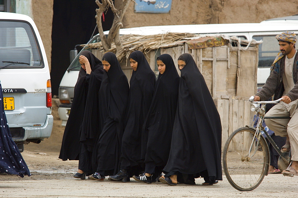 "Tajik girls wear full length Iranian style veils, called ""abbaya"" as they walk to school through the bazaar of  Turghondi, a town on the border with Turkmenistan, in the northern part of Herat Province."