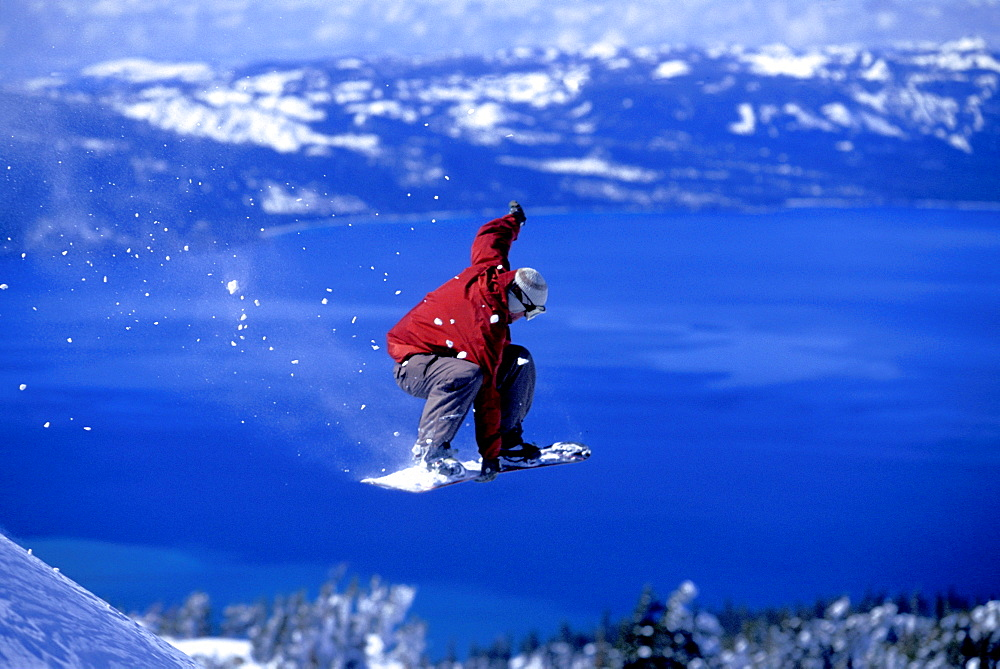Mikey Wier throwing a grab off of a cliff while snowboarding above Lake Tahoe at Heavenly Mountain Resort in South Lake Tahoe, California.