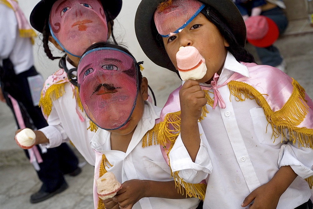 Masked kids eat ice cream during the fiesta of Corpus Christi, in Alangasi Ecuador, on June 10, 2007.   The fiesta of Corpus Christi is a mixture of Spanish, or Catholic, customs and pre-Colombian or indigenous customs.  It takes place during the harvest