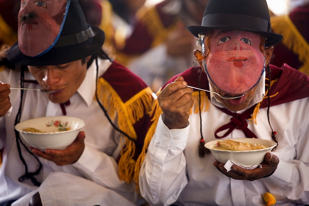 Men take off their masks to eat traditional food during the fiesta of Corpus Christi, in Alangasi Ecuador, on June , 2007.   The fiesta of Corpus Christi is a mixture of Spanish, or Catholic, customs and pre-Colombian or indigenous customs.  It takes plac