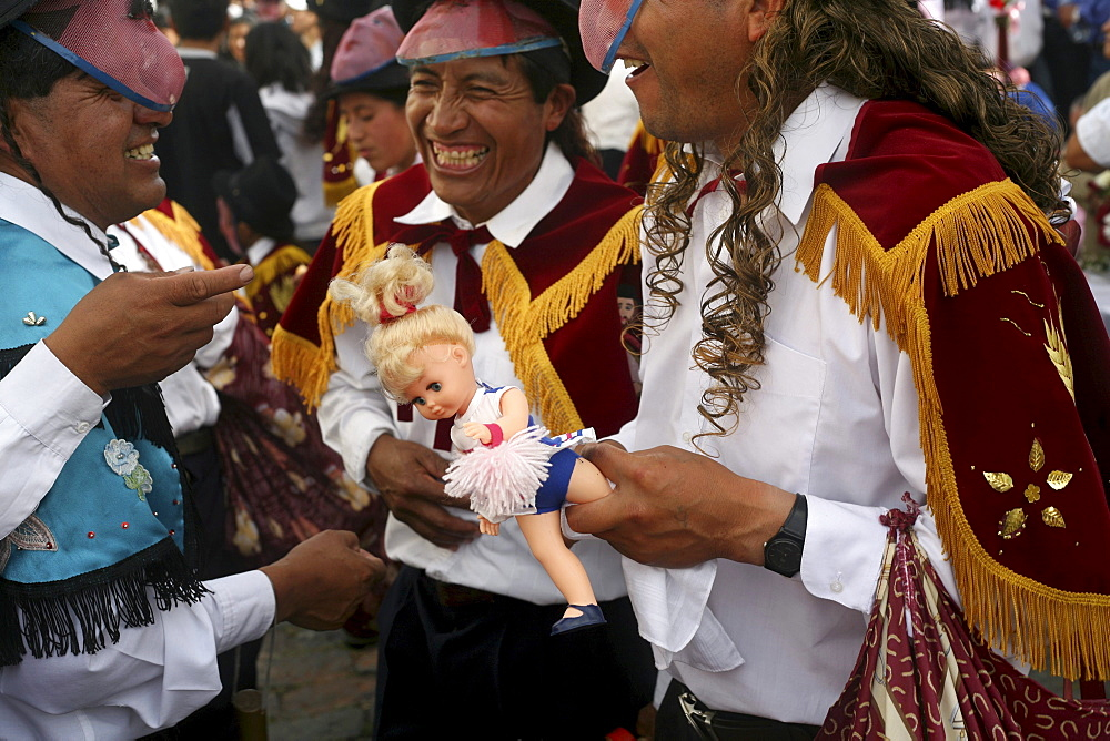 Masked men carry dolls and drink alcohol during the fiesta of Corpus Christi, in Alangasi Ecuador, on June 10, 2007.   The fiesta of Corpus Christi is a mixture of Spanish, or Catholic, customs and pre-Colombian or indigenous customs.  It takes place duri