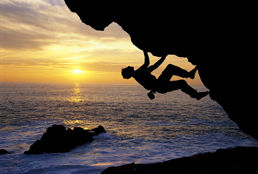 Kevin Jorgesen bouldering at sunset on the craggy Sonoma County coastline in Northern California. Bouldering is a kind of  gymnastic rock climbing in which the climber uses his hands and feet to scale reasonably small rocks without a rope or other equipme