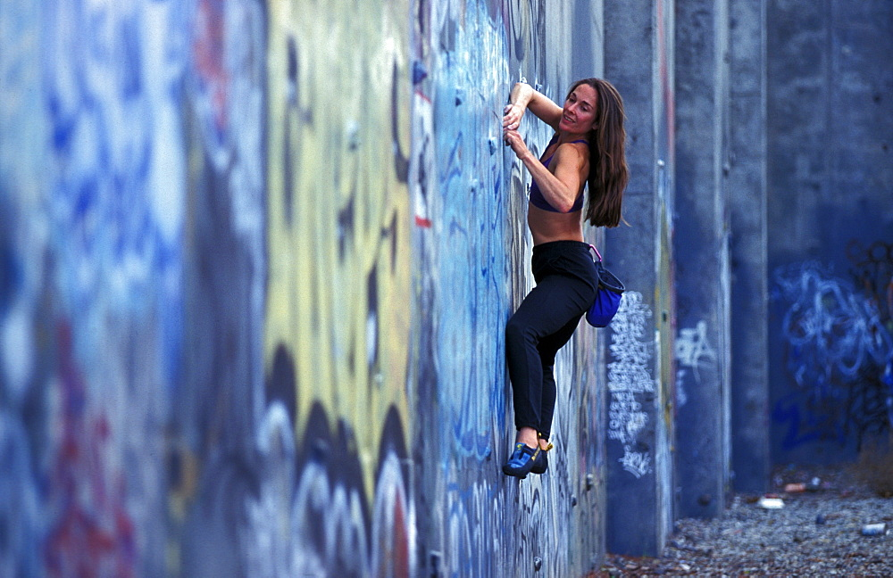 Sabina Allemann buildering on a graffiti covered wall in San Jose, California.