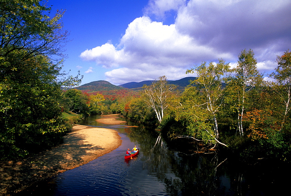 Rob Center and kay Henry paddle their canoe on the Upper Ammonoosuc River in far northern New hampshire on a beautiful autumn day. The river is a part of the Northern Forest Canoe Trail, which was founded by Rob and Kay.