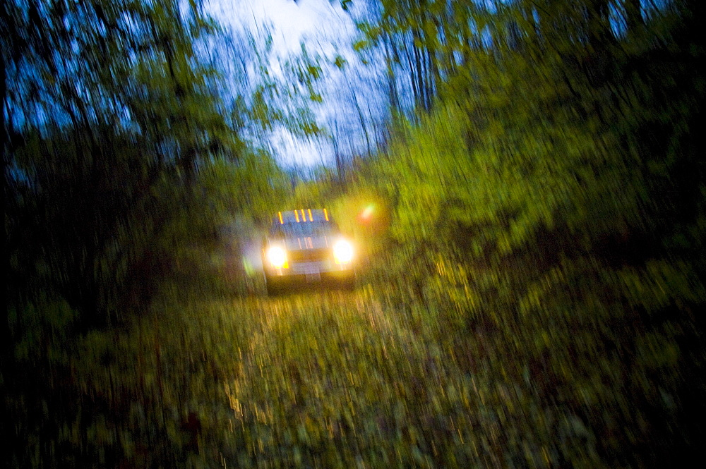 Hamilton, Ohio - November 22: A truck with headlights on drives down a dark, country road.