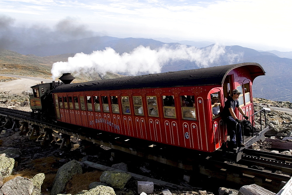Mount Washington Cog Railway coach and steam engine head down from the summit of Mt Washington, with the unidentified brakeman watching from the back. The world's first cog railway was built and put in service in 1869 by Sylvester Marsh, and has remained