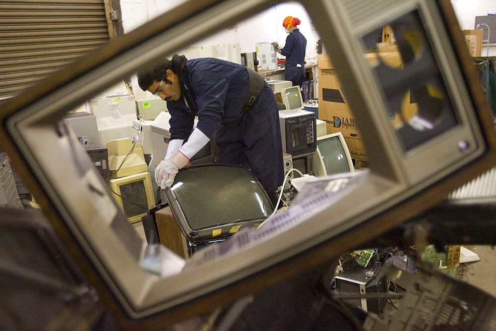 At CRT Recycling in Brockton, Massachusetts, workers look over electronics collected locally to determine what is valuable to recycle in house and what is sent overseas. - 857-66629