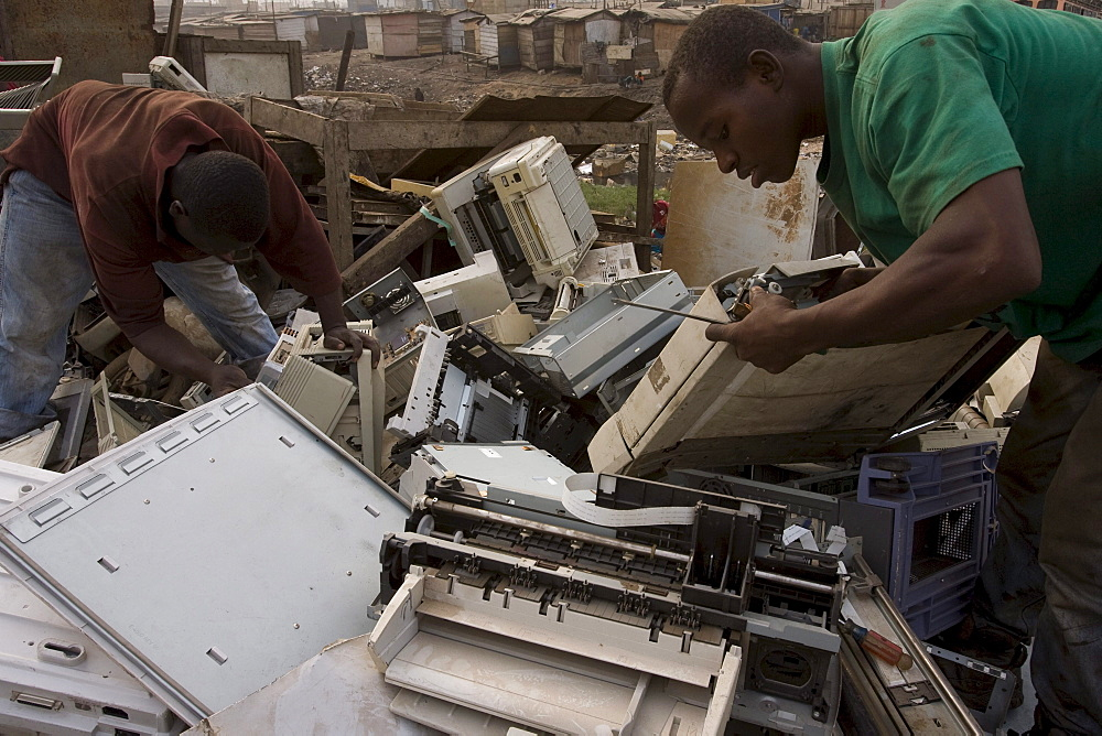 Burning of computer wire and parts to recover copper and other metals in Accra, Ghana. The computers are shipped here from Europe and the USA and some are reused but majority are dumped in Ghana. Poor workers often from the northern poorer region of Ghana