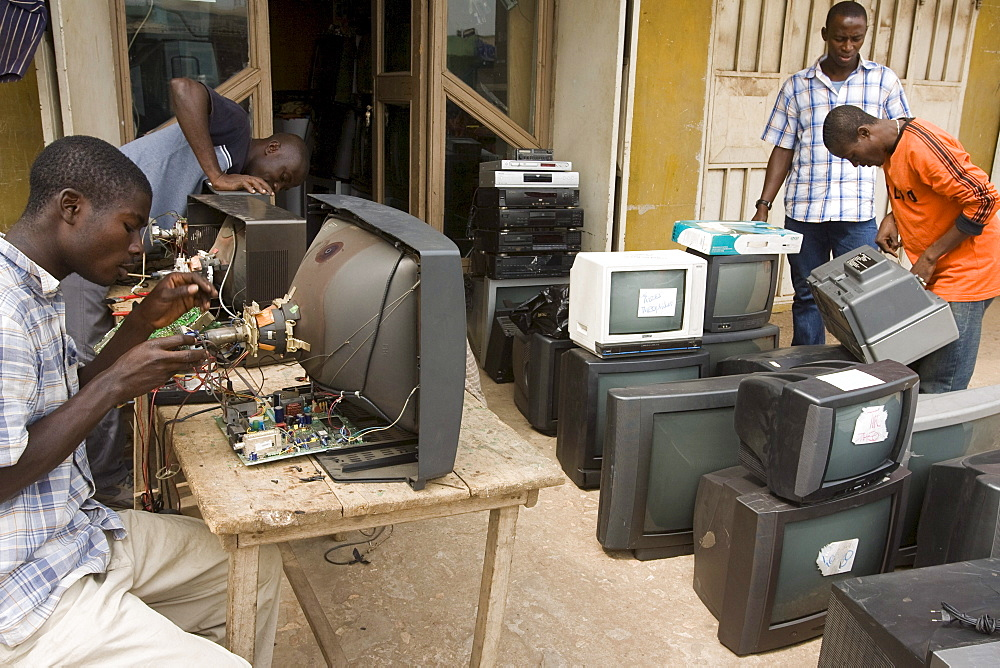 Workers repairing electronics at a shop in Accra, Ghana. The computers are shipped here from Europe and the USA and some are reused but majority are dumped in Ghana.