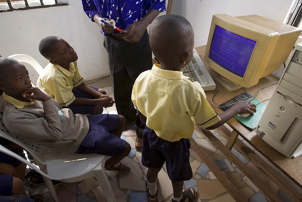 "Yinka Ogunsuyi teaches a computer class to 9-11 year olds from the Regency School in Lagos, Nigeria. He gets the computers from a contact in the USA and also buys some in Nigeria. The computer is a Pentium 3 Dell from the USA. Also at the school 2-3 year olds watch the movie ""Happy Feat"" on a Pentium 4 computer."