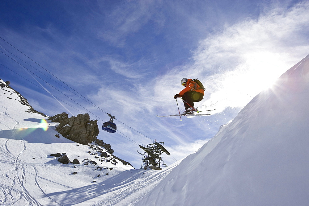 A man jumps off cornice while skiing in St. Anton am Arlberg, Austria.