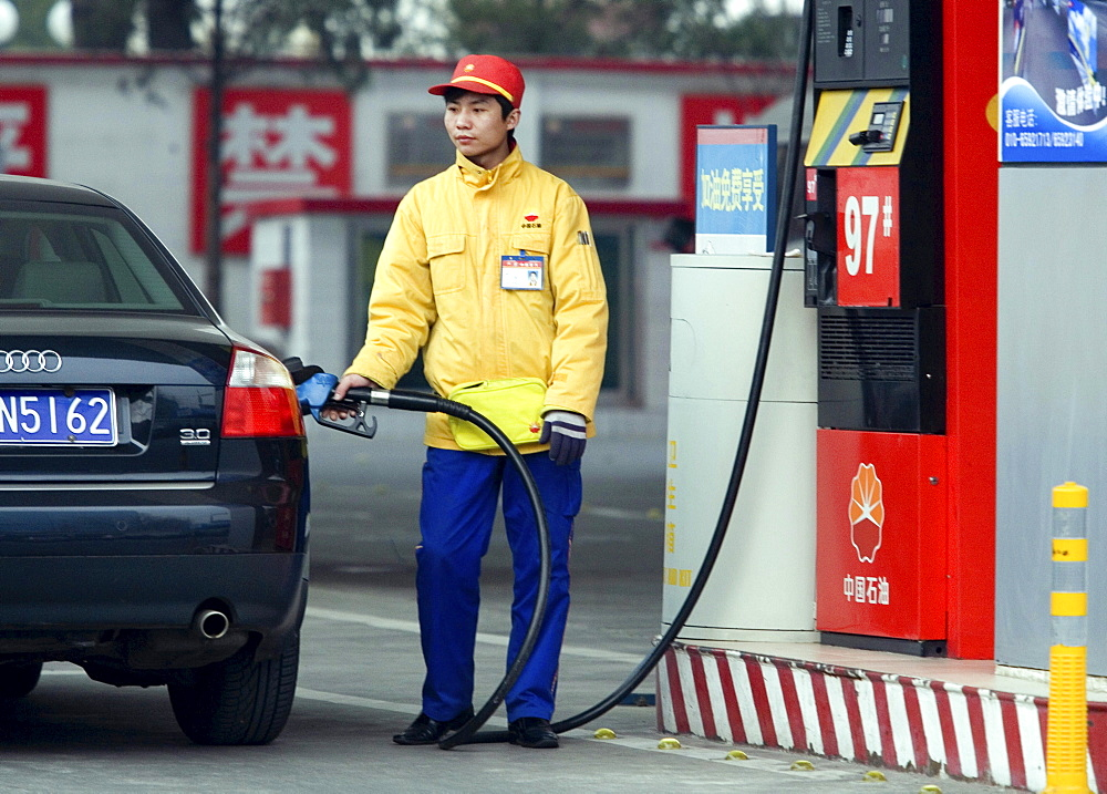 A Chinese gas station attendant fills up a customer's car in Beijing. Chinese Premier Wen Jiabao promised a national plan to address climate change but avoided offering emissions caps, speaking after a parliament session where global warming barely scraped onto the agenda.