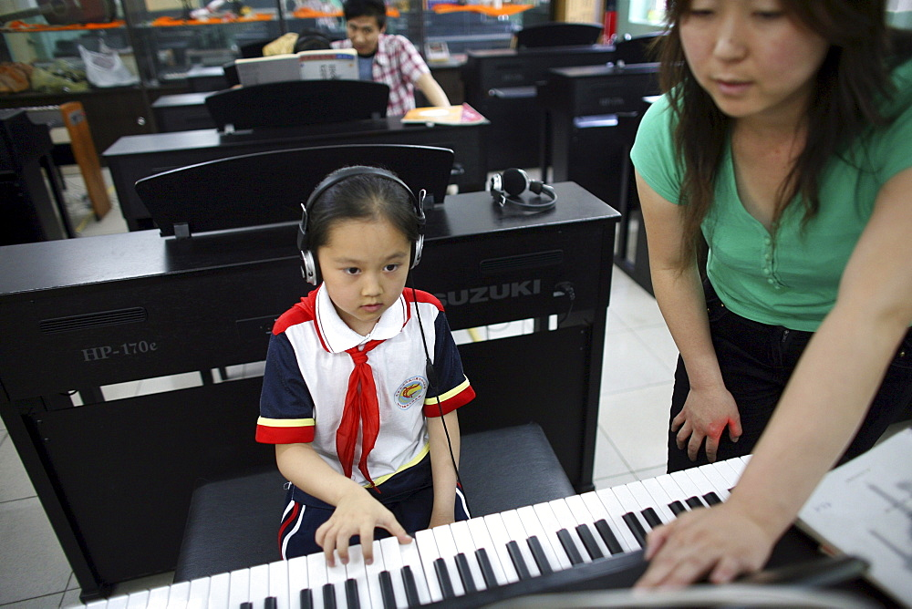 Chinese seven-year-old Shen Siyue at her weekly piano lesson at school in Beijing, China.