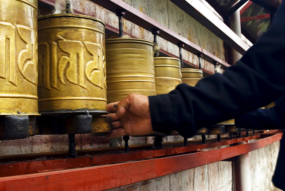 A Tibetan pilgrim spins prayer wheels in Lhasa, Tibet Autonomous Region, China.