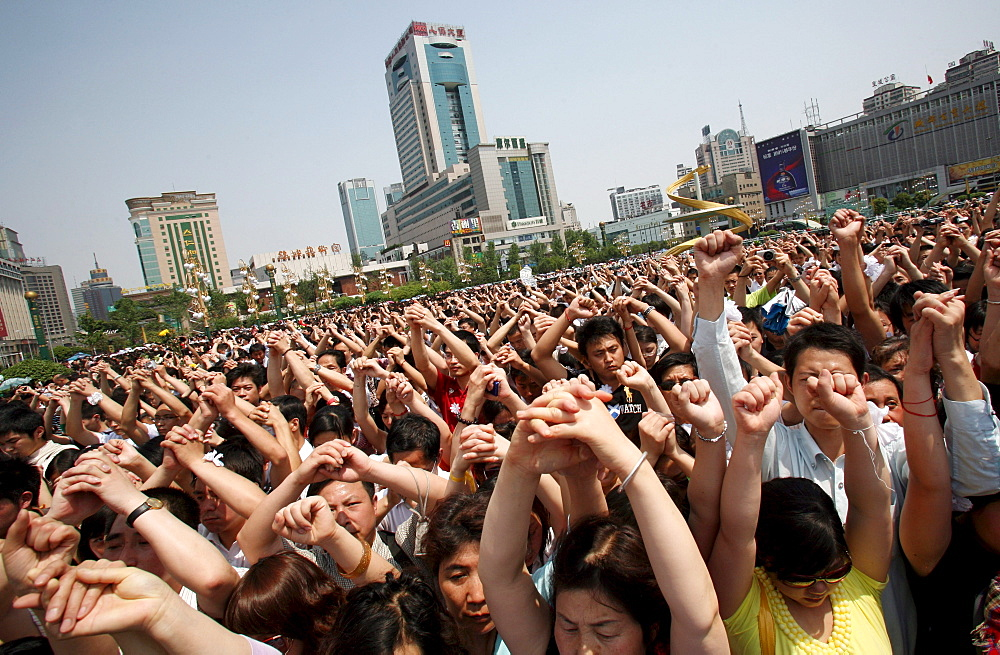 Chinese mourners hold hands in the central square of Chengdu as they observe three minutes of silence to grieve Sichuan's earthquake victims.