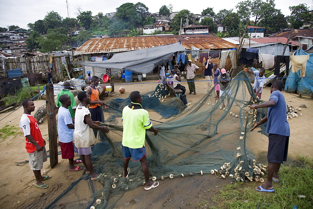 Monrovia, Liberia - September 18, 2007: Fishermen in West Point , Monrovia, Liberia sorting out, mending and picking trash out of their fishing nets. The fishing industry is an important source of employment and food for Liberians and is increasingly unde
