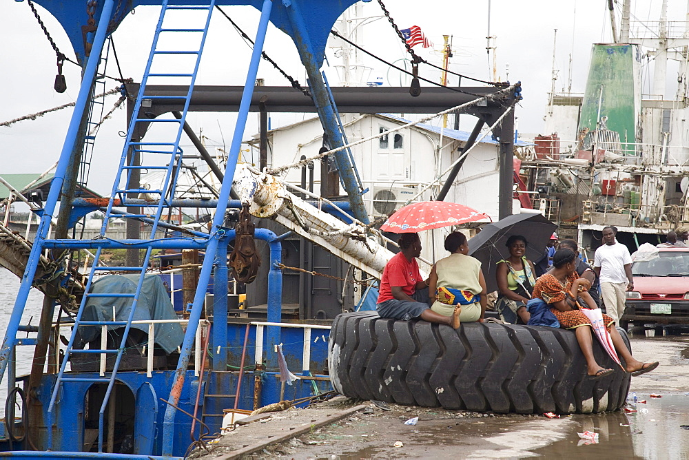 Monrovia, Liberia - September 19, 2007: Liberian women hanging out on the fishing port in Monrovia where almost all of the boats are operated by foreigners.