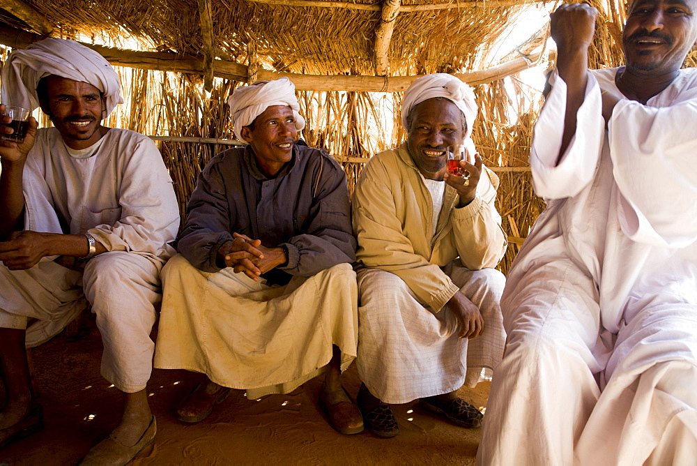 Camel traders and herders sit in a tea hut in a camel market in El Obeid, Sudan on February 16, 2006. Yussuf Gamaa, 2nd from L, is a camel herder from Darfur. About 150,000 camels cross over from Sudan into Egypt every year, the majority as cattle as an inexpensive source of protein. Today the camel is both the caravan and the cargo. Camels from this market will travel the Forty Days Road or Darb el-Arbein a 1,200 mile desert trail into Egypt and the oldest trade route in the Sahara. Desert nomads like Yussuf depend on the profitable camel trade for their livelihood.