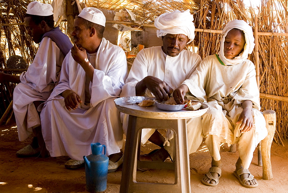 Camel traders and herders sit in a tea hut in a camel market in El Obeid, Sudan