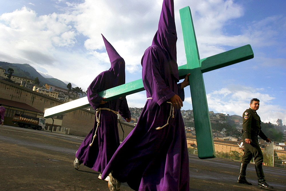 Two Cucuruchos return with a cross after a long march through the streets of Quito, Ecuador on Holy Friday, two days before Easter, on March 25, 2005.  The Cucuruchos show their dedication to Jesus by walking the streets of Ecuador while dragging chains and carrying giant crosses to repent for their sins.
