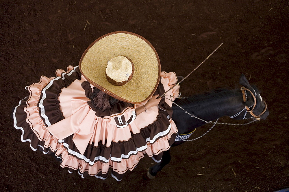 "An escaramuza from Anahuac of Tecamac team rides her horse in a rodeo competition in Mexico City, May 10, 2008. Escaramuzas are similar to US rodeos, where female competitors called ""Amazonas"" wear long skirts, and ride side saddle. Male rodeo competitors"