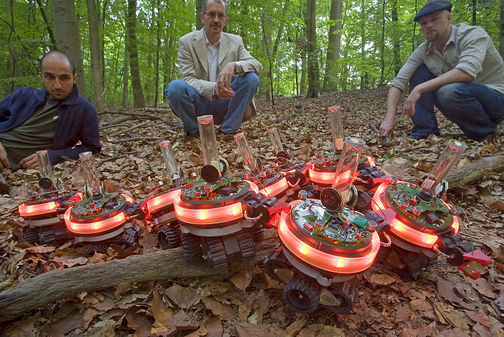 Swarm robots designed by Marco Dorigo, center, and his graduate students Universit_ Libre de Bruxelles, Brussels, Belgium. An individual robot could not cross this obstacle in the forest, but when they link together and communicate with each other(when they do this lights go on) they can cross a barrier. This was inspired by how ants link together in a group to cross barriers.