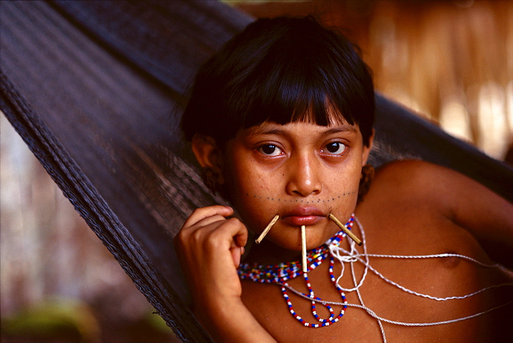Yanomami Indian girl with sticks at the corners of her mouth and just below her lower lip and bead necklaces lies in a hammock in her village in the Amazonian Forest in southern Venezuela.