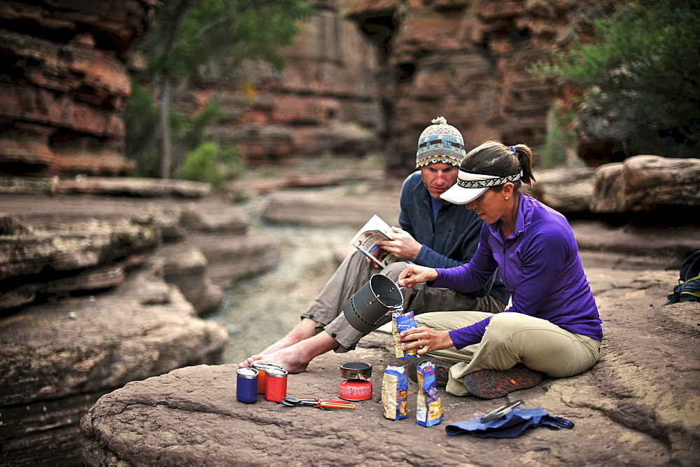 Hikers cook dinner along Deer Creek Narrows in the Grand Canyon outside of Fredonia, Arizona November 2011.  The 21.4-mile loop starts at the Bill Hall trailhead on the North Rim and descends 2000-feet in 2.5-miles through Coconino Sandstone to the level Esplanada then descends further into the lower canyon through a break in the 400-foot-tall Redwall to access Surprise Valley.  Hikers connect Thunder River and Tapeats Creek to a route along the Colorado River and climb out Deer Creek.