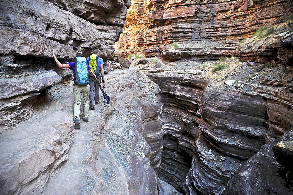 Hikers walk along Deer Creek Narrows in the Grand Canyon outside of Fredonia, Arizona November 2011.  The 21.4-mile loop starts at the Bill Hall trailhead on the North Rim and descends 2000-feet in 2.5-miles through Coconino Sandstone to the level Esplanada then descends further into the lower canyon through a break in the 400-foot-tall Redwall to access Surprise Valley.  Hikers connect Thunder River and Tapeats Creek to a route along the Colorado River and climb out Deer Creek.