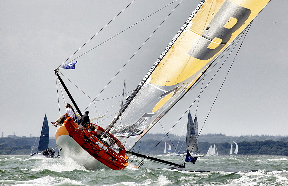 The IMOCA Open 60 PRB crewed by Vincent Riou and Jean Le Cam racing and winning the around the Isle of Wight Artemis Challenge, Cowes, England.