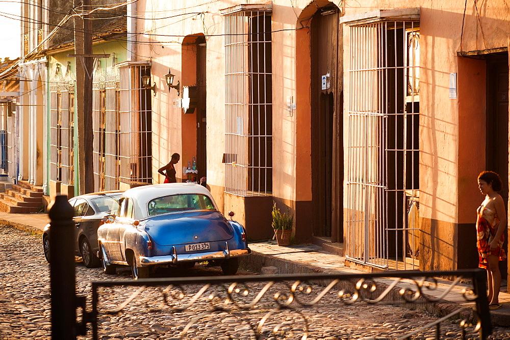 The setting sun illuminates a street scene in Trinidad, Cuba.