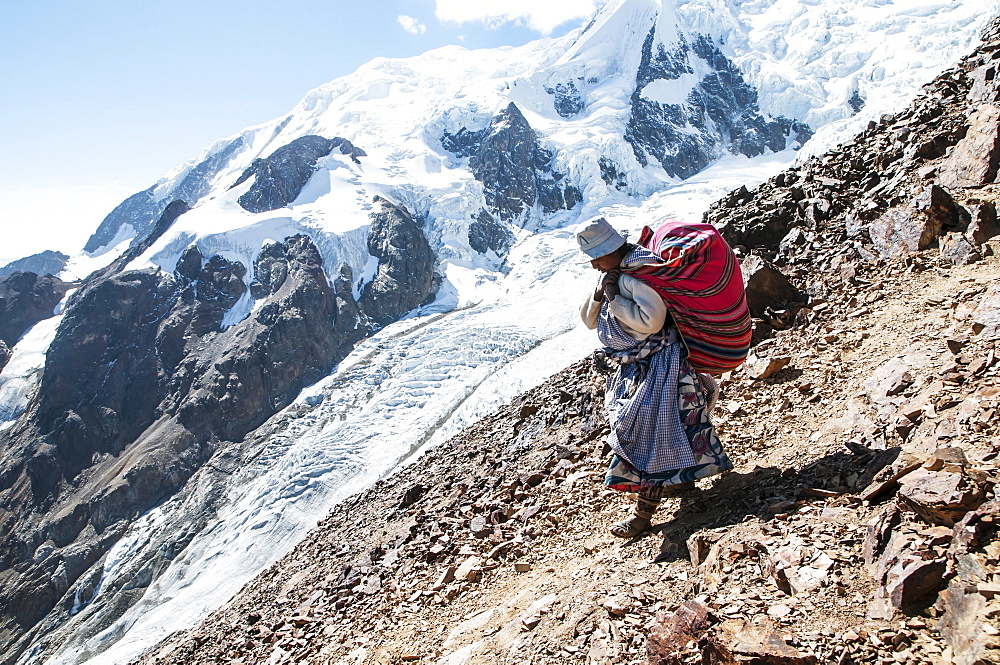 An Aymaran women porters carry loads of climbing gear at 16,000ft on Illimani a 20,000ft peak in the Bolivian Andes.
