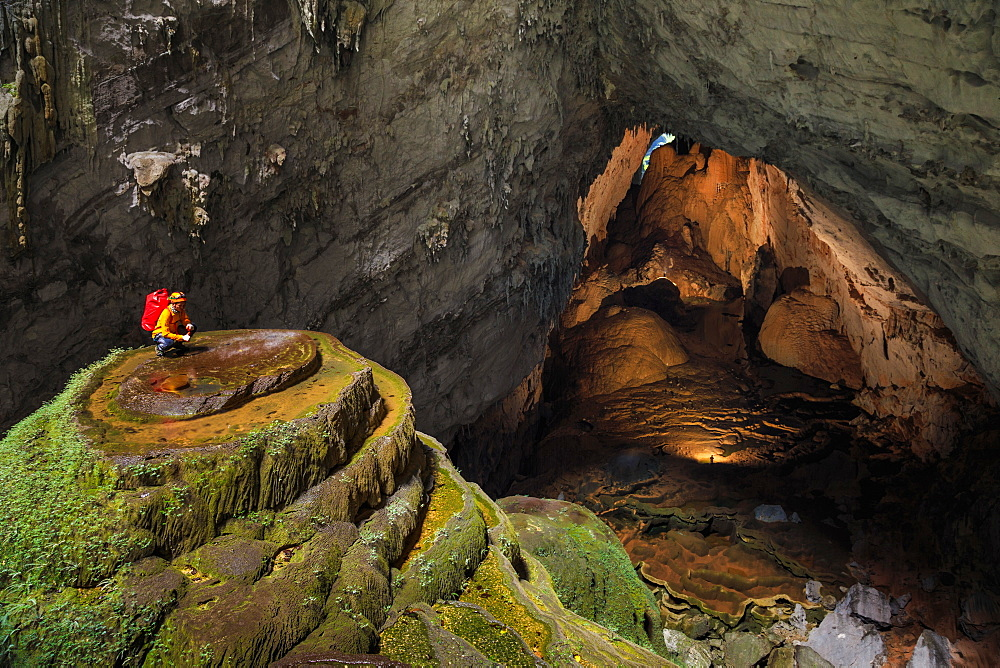 A cave explorer on a speleothem at the first doline, or skylight, in Hang Son Doong while two other explorers illuminate a large passage leading to the second doline 1.5 kilometers away.