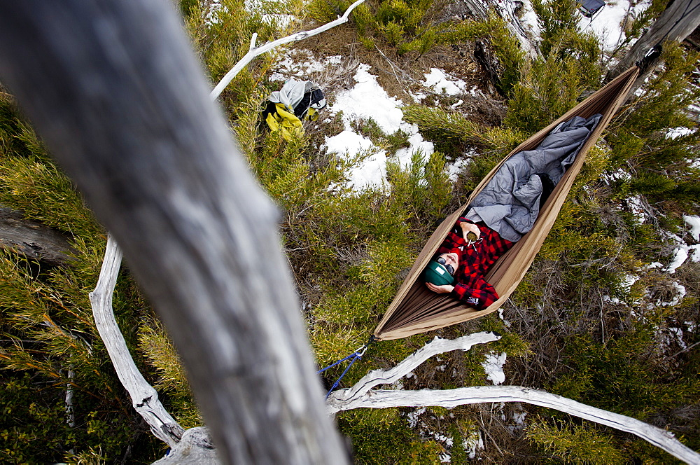 Man lays in hammock and enjoys a warm cup of Mate.
