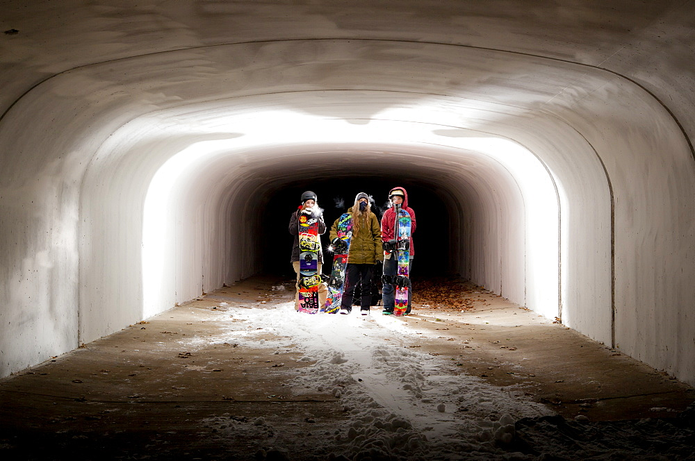 Three snowboarder girls stand holding there snowboards in tunnel at night.