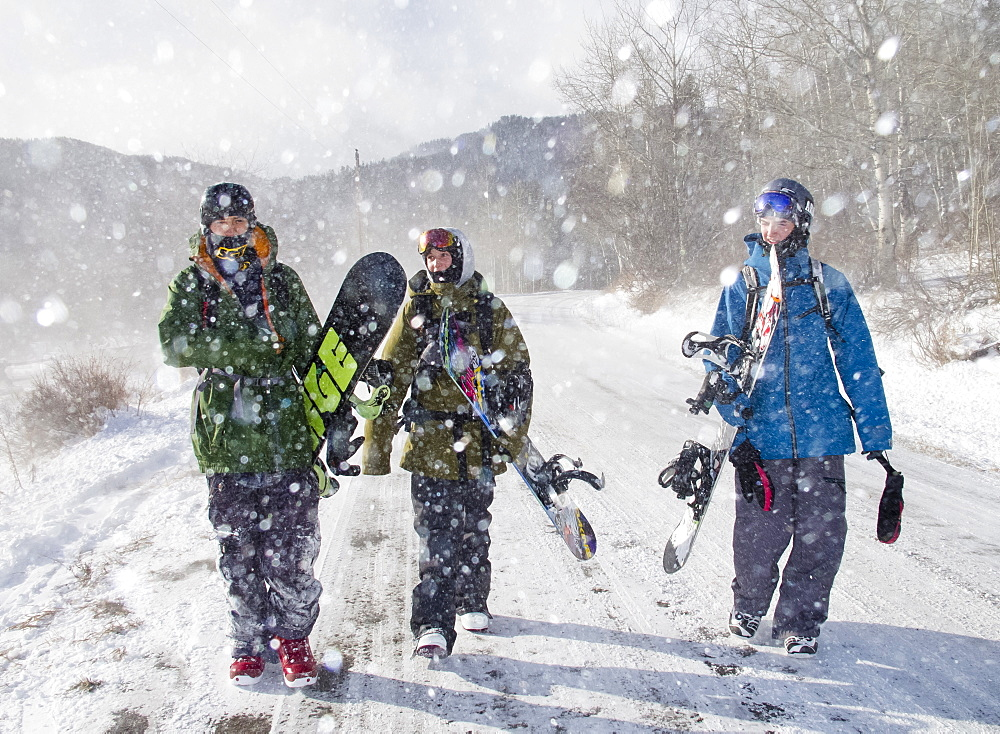 Three snowboarders walk down a snowy road after riding Teton Pass