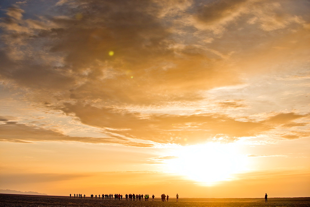 Competitors in the Salt Flats 100 run across the Bonneville Salt Flats at sunrise in Bonneville, Utah.