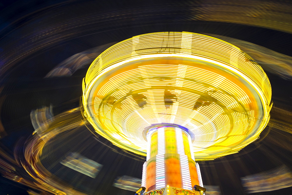 Long exposure of Chair Swing ride at Hamburger DOM funfair at night, St. Pauli, Hamburg, Germany