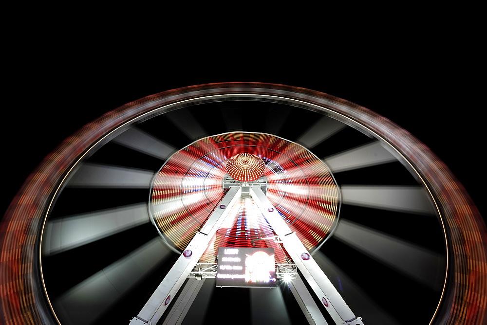 Long exposure of illuminated ferris wheel at Hamburger DOM funfair at night, St. Pauli, Hamburg, Germany
