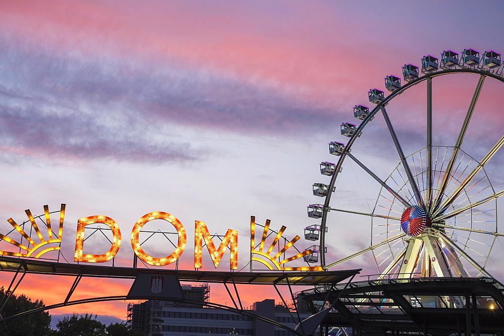 Illuminated entrance to Hamburger DOM funfair and ferris wheel at sunset, St. Pauli, Hamburg, Germany