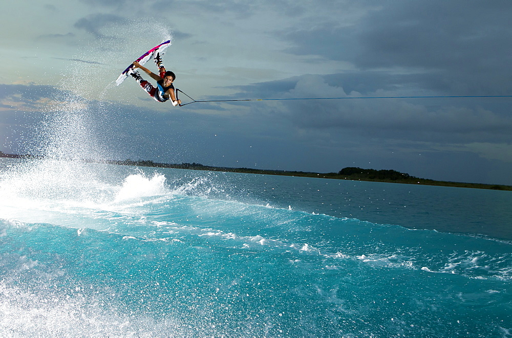 A young rider performs a hand grab while wake boarding at sunset time in Bacalar, Quinatana Roo, Mexico