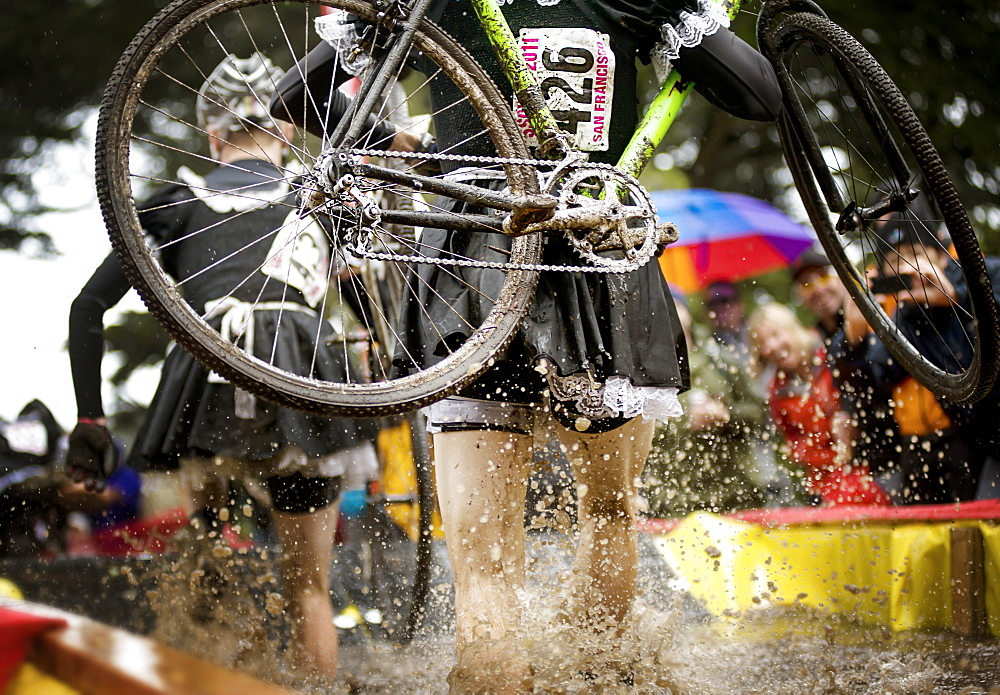 cyclocross racer steps through water obstacles...San Francisco, California