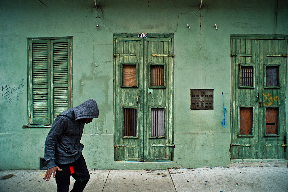 A man in a hooded sweatshirt walks down the street in the French Quarter of New Orleans, Louisiana.
